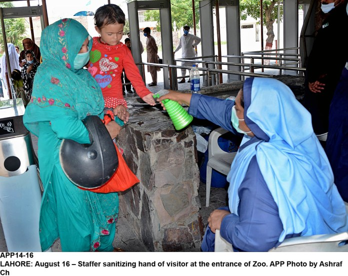 LAHORE: August 16 – Staffer sanitizing hand of visitor at the entrance of Zoo. APP Photo by Ashraf Ch