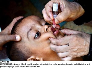 HYDERABAD: August 16 – A health worker administering polio vaccine drops to a child during anti polio campaign. APP photo by Farhan Khan