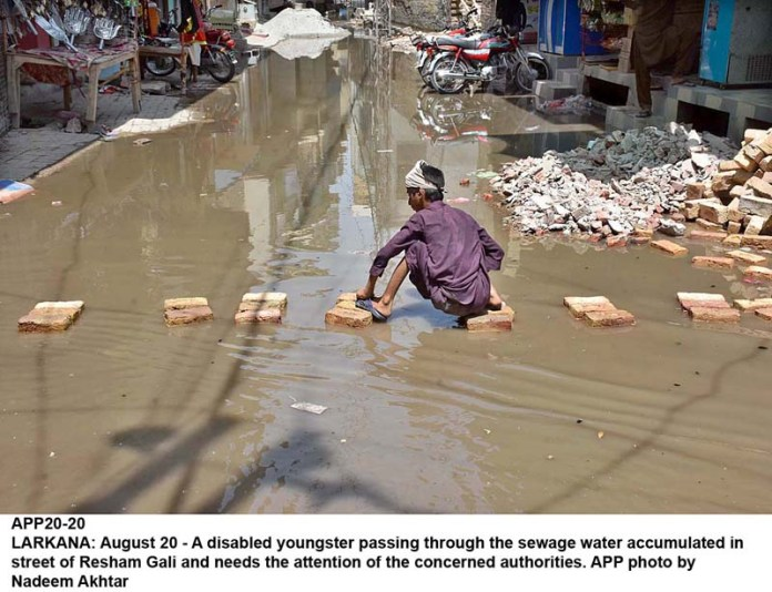 LARKANA: August 20 - A disabled youngster passing through the sewage water accumulated in street of Resham Gali and needs the attention of the concerned authorities. APP photo by Nadeem Akhtar