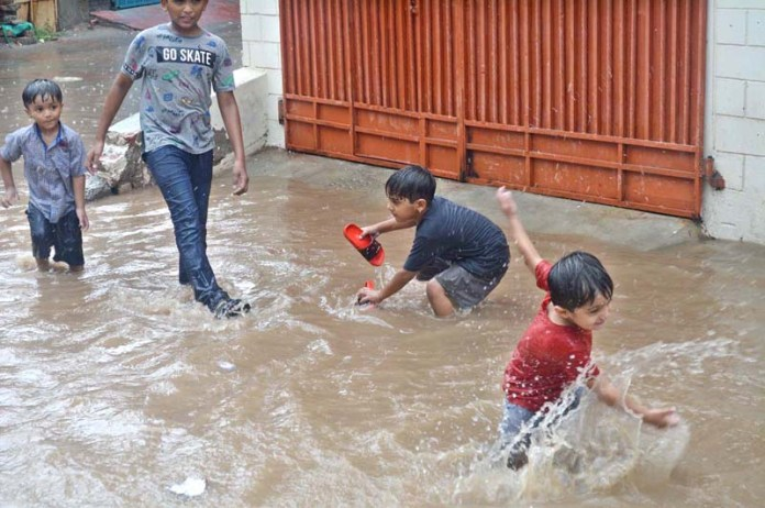 SARGODHA: August 27 - Children enjoying play in rain water during rain in the city. APP photo by Hassan Mahmood