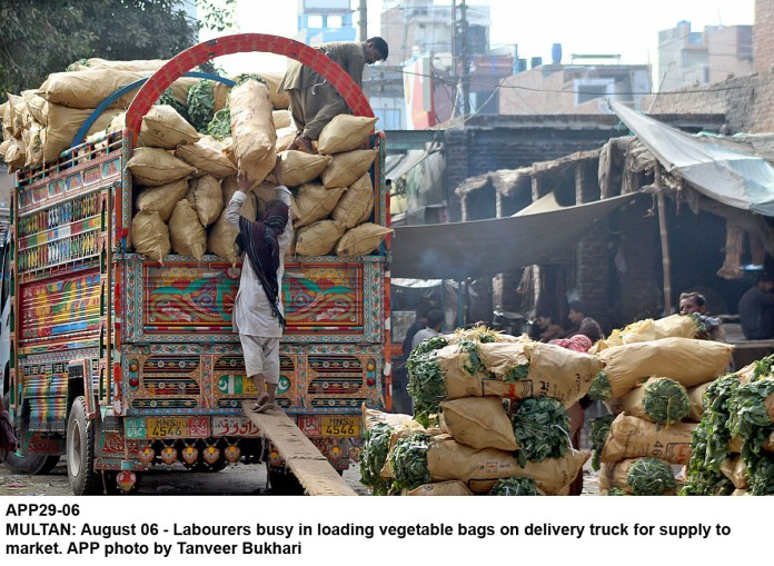 MULTAN: August 06 - Labourers busy in loading vegetable bags on delivery truck for supply to market. APP photo by Tanveer Bukhari