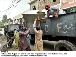 FAISALABAD: August 17 - Staff of Municipal Corporation take away material during anti encroachment campaign. APP photo by Muhammad Waseem