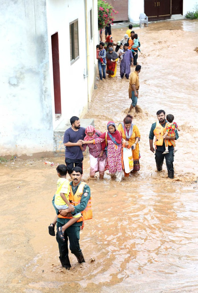RAWALPINDI: August 27 - Rescue workers carry children shift them to safer places following monsoon rain and overflowed Nullah Lai passing through the area triggered floods and forcing people to move along with their belongings to safer places in the outskirts of the city. APP photo by Abid Zia