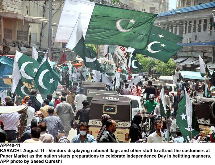 KARACHI: August 11 - Vendors displaying national flags and other stuff to attract the customers at Paper Market as the nation starts preparations to celebrate Independence Day in befitting manners. APP photo by Saeed Qureshi