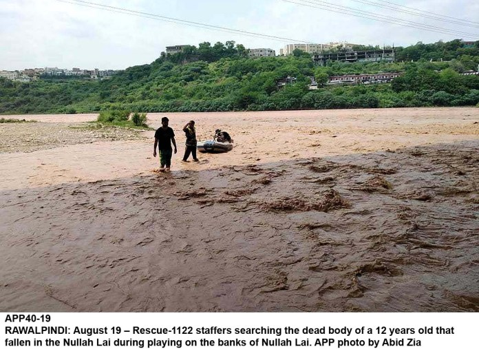 RAWALPINDI: August 19 – Rescue-1122 staffers searching the dead body of a 12 years old that fallen in the Nullah Lai during playing on the banks of Nullah Lai. APP photo by Abid Zia