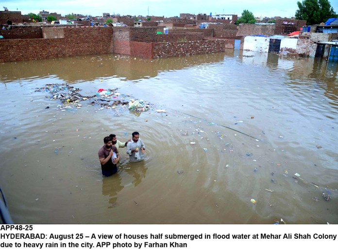 HYDERABAD: August 25 – A view of houses half submerged in flood water at Mehar Ali Shah Colony due to heavy rain in the city. APP photo by Farhan Khan