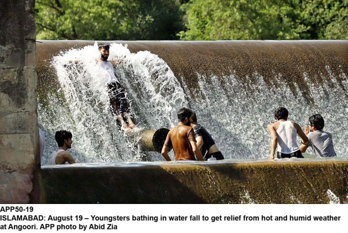 ISLAMABAD: August 19 – Youngsters bathing in water fall to get relief from hot and humid weather at Angoori. APP photo by Abid Zia