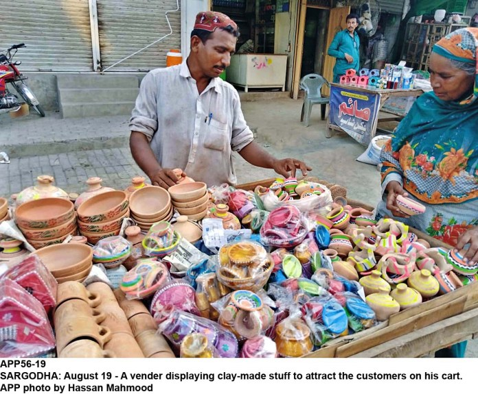 SARGODHA: August 19 - A vender displaying clay-made stuff to attract the customers on his cart. APP photo by Hassan Mahmood