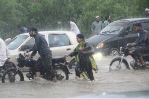 KARACHI: August 27 – Commuters struggling to pass through rain water accumulated on road during heavy rain in Provincial Capital City. APP photo by Syed Abbas Mehdi