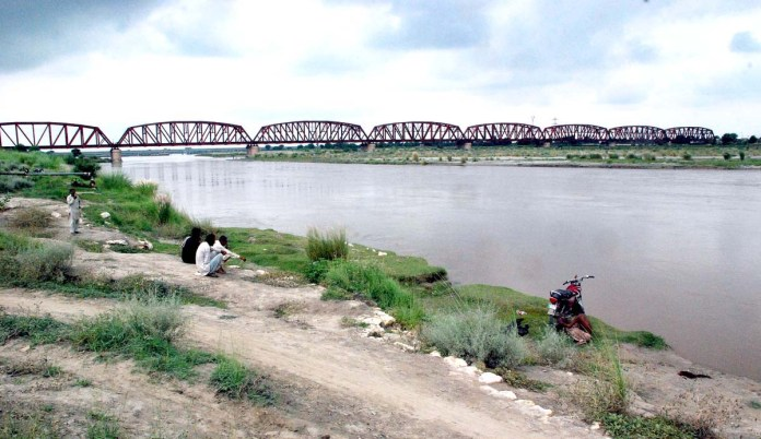 BAHAWALPUR: September 05 - A group of people sitting on the bank of River Satluj as the water level is high due to heavy rain. APP photo by Hassan Bukhari