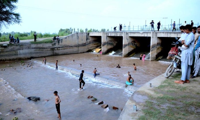 LAHORE: September 11 - Children bathing in Noor Pur canal to relief from humid weather. APP photo by Ashraf Ch