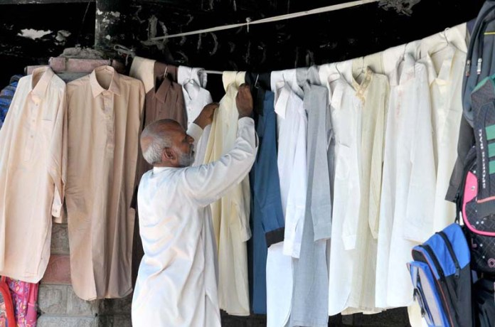 ISLAMABAD: September 20 – A vendor displaying used clothes to attract the customers outside Sunday Bazar Aabpara. APP photo by Saeed-ul-Mulk