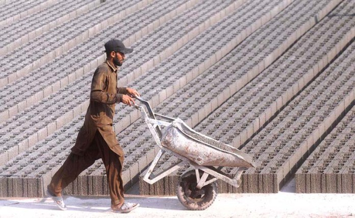 ISLAMABAD: September 11 – A worker with his handbarrow at his workplace at Bara Kahu area. APP photo by Irfan Mahmood