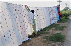 LAHORE: September 14 - Vendor busy in arranging and displaying bed sheets to attract the customers at his roadside setup. APP photo by Ashraf ChLAHORE: September 14 - Vendor busy in arranging and displaying bed sheets to attract the customers at his roadside setup. APP photo by Ashraf Ch