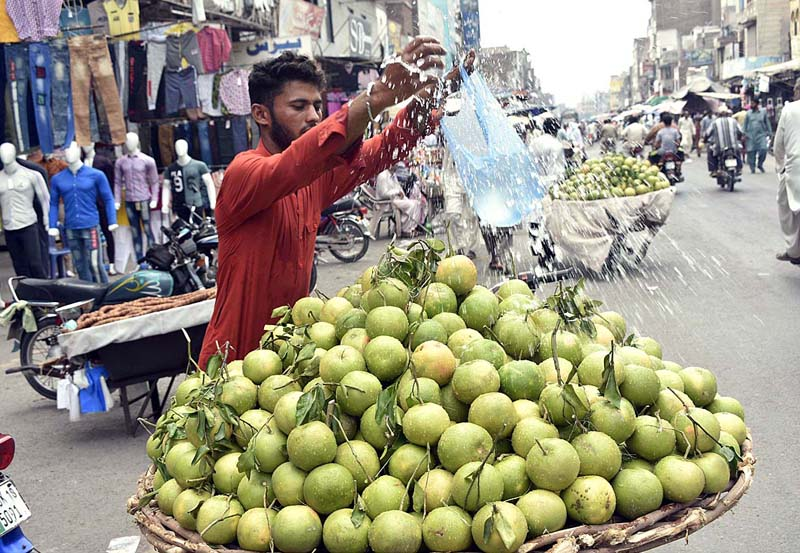 FAISALABAD: September 16 - A vender showering water on seasonal fruits to keep it fresh and attract the customers. APP photo by Muhammad Waseem