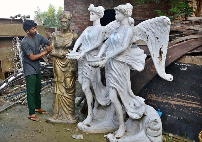 LAHORE: September 14 – A worker busy in arranging and displaying statues to attract the customers. APP Photo by Ashraf Ch
