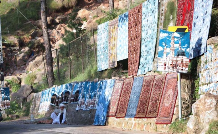 MURREE: September 28 - A vendor displaying carpets to attract the customers at his roadside setup at muree. APP photo by Abid Zia