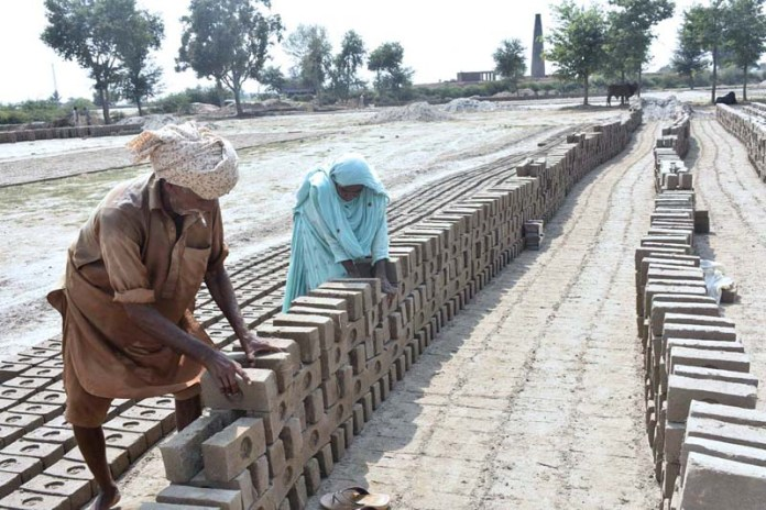 FAISALABAD: September20 – An aged couple busy in work at a local kiln to earn livelihood. APP photo by Muhammad Waseem