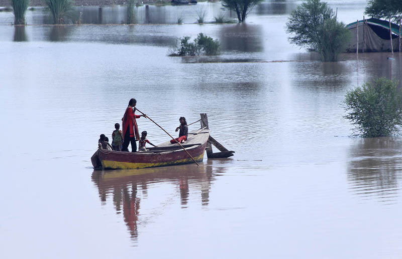 MULTAN: September 04 – Flood affected family traveling on the boat heading towards safe areas near Basti Mohammad Pur Ghot. APP photo by Tanveer Bukhari