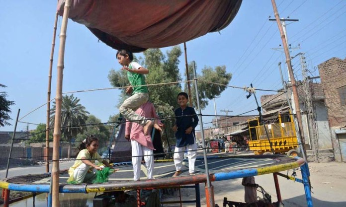 SARGODHA: September 28 - Children enjoying jump on trampoline at Jinnah Colony. APP photo by Hassan Mahmood