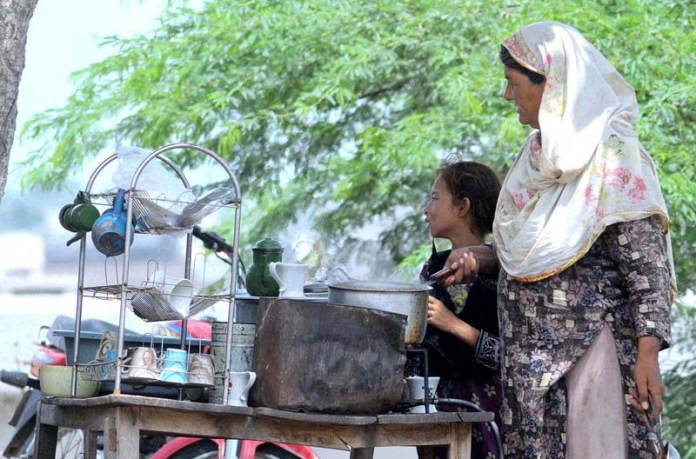 MULTAN: September 04 - A women vendor preparing tea for customers at her roadside setup. APP photo by Qasim Ghauri