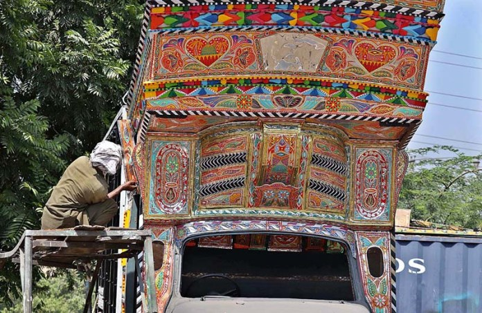 RAWALPINDI: September 10 - A worker painting the delivery truck's body at his workplace near Pirwadai. APP photo by Abid Zia