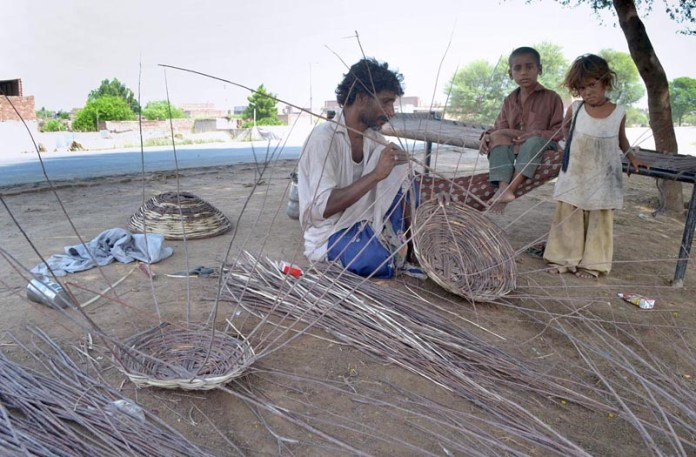MULTAN: September 07 – A gypsy person busy in making basket from dry tree branches at roadside. APP photo by Safdar Abbas