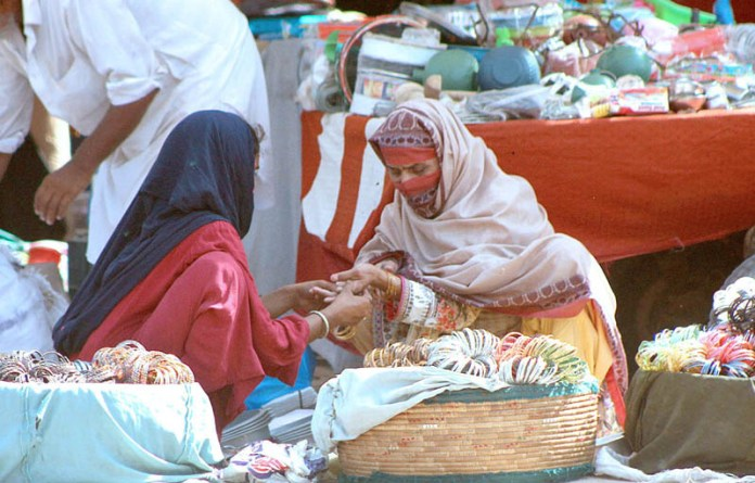 MULTAN: September 18 - A female customer being wore bangles from a roadside female vendor at Friday Bazaar. APP photo by Tanveer Bukhari