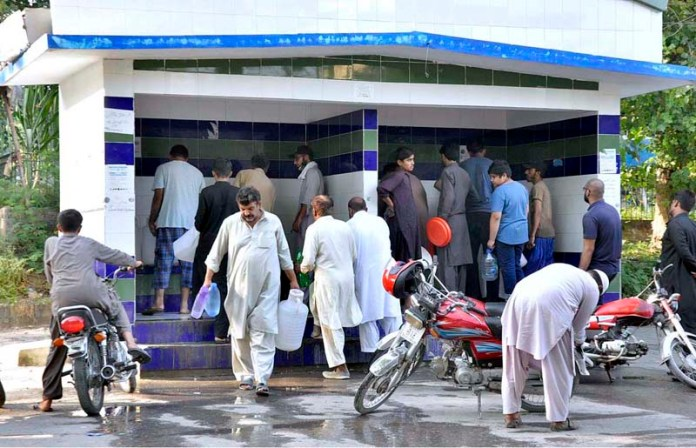 ISLAMABAD: September 19 – A large number of people filling their pots with clean drinking water through a filtration plant. APP photo by Saleem Rana