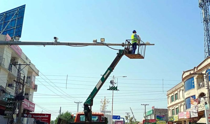 RAWALPINDI: September 30 - A technician installing CCTV cameras at Ghouri Town. APP photo by Abid Zia