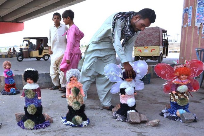 HYDERABAD: September 17 – A vendor displaying and arranging dolls to attract the customer at Eidgah Road. APP photo by Akram Ali