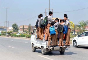 PESHAWAR: September 21 - Students standing on back of passenger van may cause any mishap and need the attention of concerned authorities. APP photo by Shaheryar Anjum