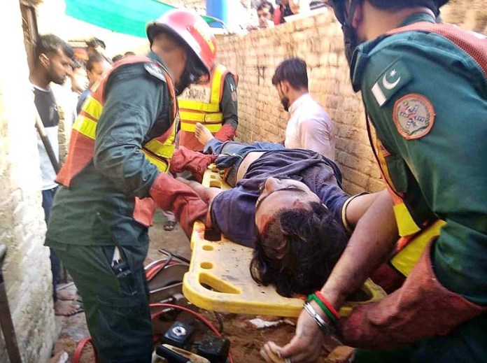 SIALKOT: September 08 - Rescue 1122 staffers busy in rescue operations for buried under the rubbles after a roof of mud house collapsed at Fatahha Gharah. APP Photo by Munir Butt
