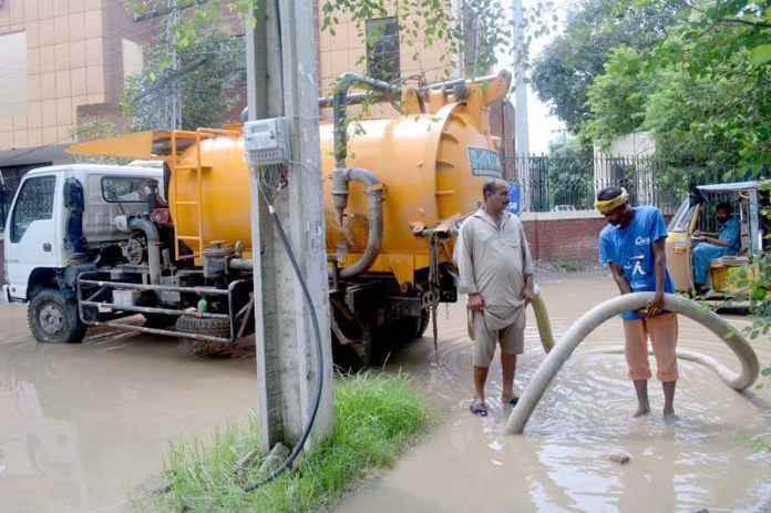 SARGODHA: September 03 - TMA workers busy in removing rain water accumulated at Stadium Food Street. APP photo by Hassan Mahmood