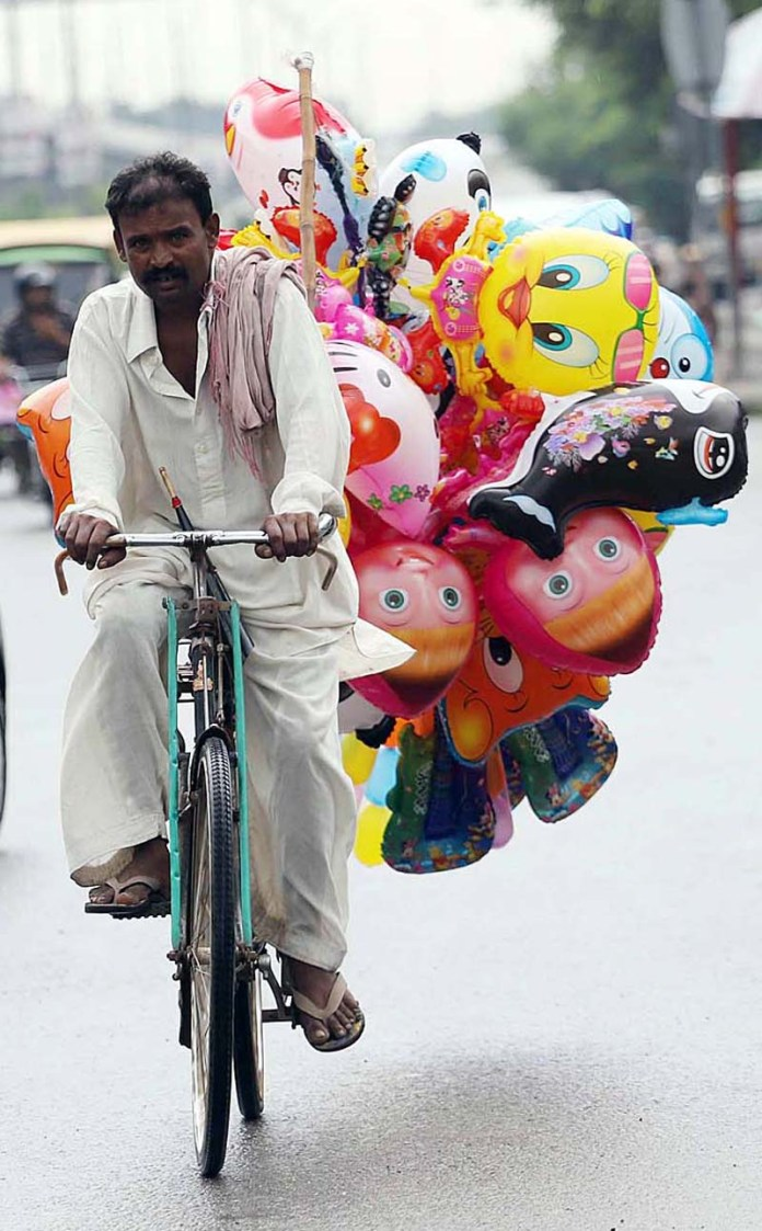 RAWALPINDI: September 18 – A street vendor displaying toy shaped balloons to attract the customers on his cycle. APP photo by Abid Zia