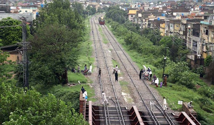 RAWALPINDI: September 18 – People walking on the rail tracks as a railway engine approaching on the same tracks may cause any mishap and needs the attention of concerned authorities. APP photo by Abid Zia