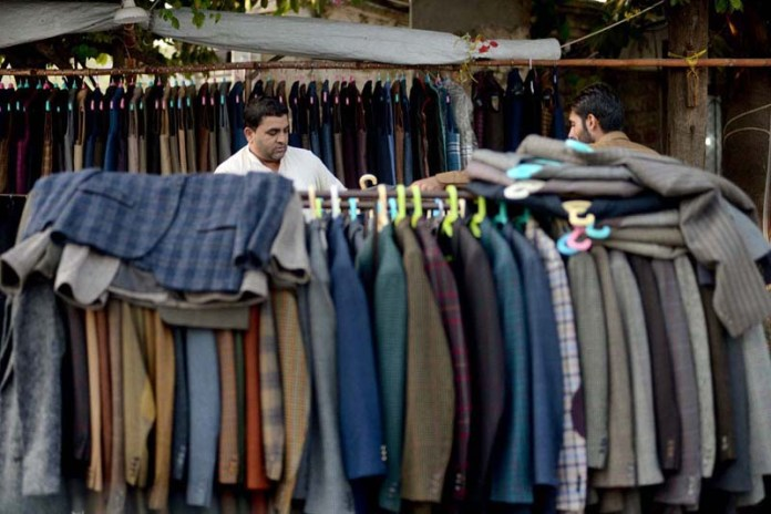 ISLAMABAD: October 11 - A man selecting overcoat from a vendors setup in G9 Markaz. APP photo by Irshad Sheikh