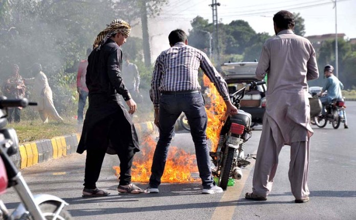 ISLAMABAD: October 04 – People struggling to control on fire caught by a motorbike near Convention Centre. APP photo by Irshad Sheikh