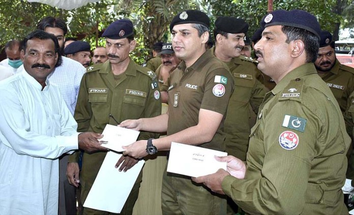 FAISALABAD: October 31 - SSP CIA Bilal Iftikhar handing over keys of stolen motorcycles and cars recovered arrested seven members of vehicle lifters gang. APP photo by Muhammad Waseem