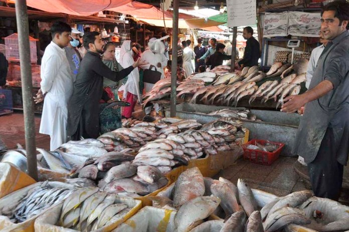 ISLAMABAD: October 18 - People purchasing fish from vendor at stall in Sunday Bazaar. APP photo by Saleem Rana
