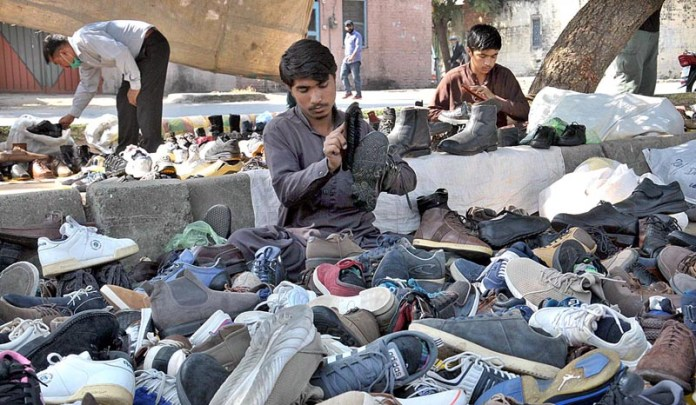 ISLAMABAD: October 20 – Vendors displaying old footwear to attract the customers at their roadside setup. APP photo by Saeed-ul-Mulk