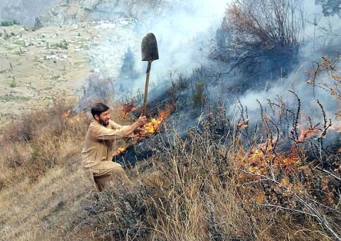 GILGIT: October 15 - A persons struggling to extinguish fire at Talu Roundu area. APP Photo by Ashraf Hussain