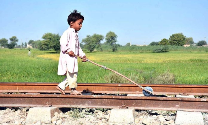 LARKANA: October 13 – A child playing on the rail tracks near Din Mohammad Chandio Village. APP photo by Nadeem Akhtar