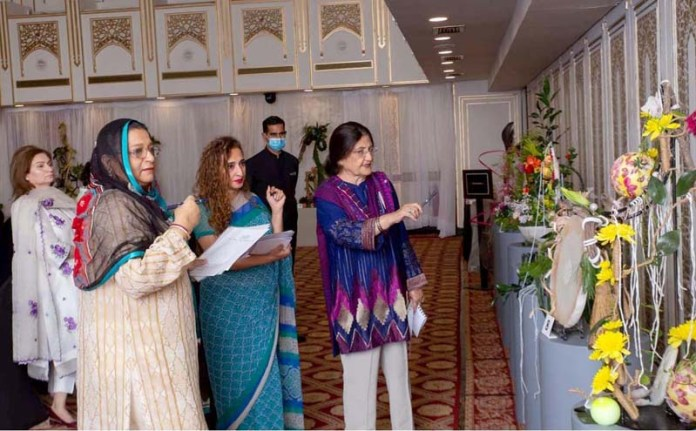 ISLAMABAD: October 18 – Women visitors keenly viewing floral art exhibition organized by Floral Art Society Orchid Club Islamabad. APP