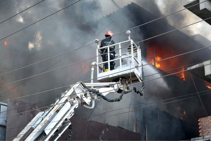 LAHORE: October 18 – Fire fighters struggling to extinguish fire erupts in Hafeez Center. APP photo by Ashraf Ch