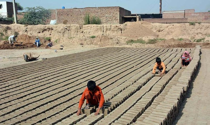 FAISALABAD: October 14 – A labourer family preparing raw bricks at a kiln. APP photo by Tasawar Abbas