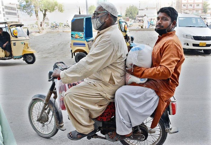 KARACHI: October 28 – Motorcyclists on the way while carrying flour bag after purchasing on subsidized rates from utility store in Provincial Capital. APP Photo by M Saeed Qureshi