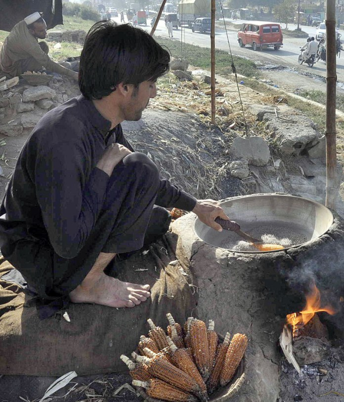 ISLAMABAD: October 10 – Vendors roasting corns to attract the customers at their roadside setup near IJP Road. APP photo by Saleem Rana