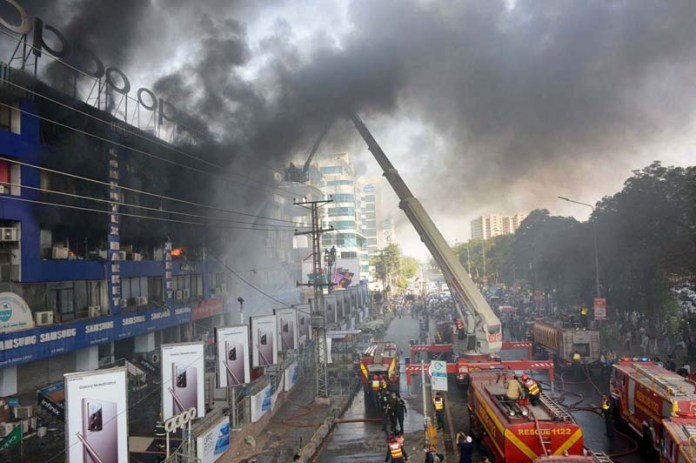 LAHORE: October 18 – Fire fighters struggling to extinguish fire erupts in Hafeez Centre. APP Photo by Rana Imran