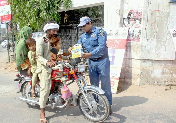MULTAN: October 23 - Traffic warden distributing gift boxes among the motorcyclists during traffic awareness campaign organized by City Traffic Police. APP photo by Tanveer Bukhari